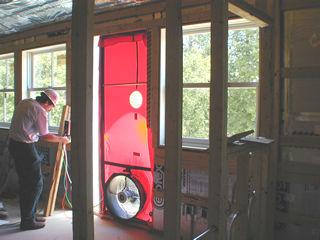 Technician conducting a blower door test & FOAM-TECH: Diagnostics and Testing Services - Blower Door Test